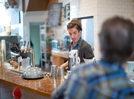 Coffee shop employee at brick and mortar business prepares coffee behind counter for waiting customer