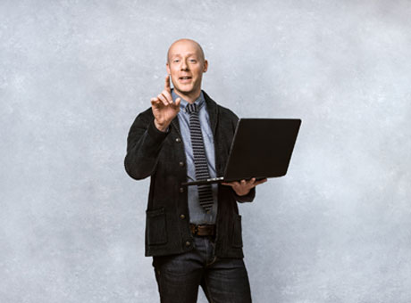 Male professional holding laptop computer discusses accounting tips in front of grey backdrop