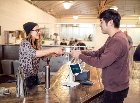 A friendly server handing coffee to a happy customer who may leave good reviews on Yelp