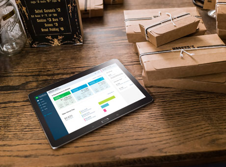 Tablet with small business terms in view sitting on desk near packages in retail storeroom