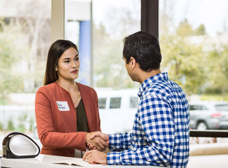 A business owner shakes hand with a client after saving the client relationship by mediating a business dispute