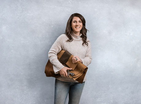 Female brand ambassador poses for photo by backdrop with briefcase in hand