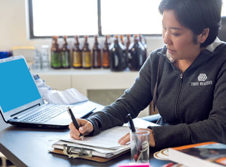 Female in organized office writing on clipboard with laptop open