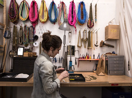 Small business owner and jewelry maker in workshop earning weekly salary