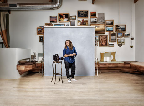 Store owner posing for business rebranding photo shoot with framed art on wall