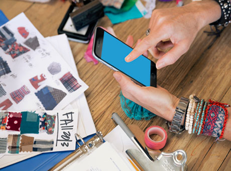 Female using smartphone to build customer relationships on desk near clothing designs