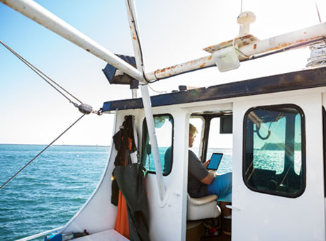 Fisherman on boat running small business using tablet while at sea