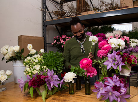 Male floral shop employee working at product flipping business arranges flowers in vases on table