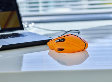 Computer mouse and monitor on office desk of non-traditional business