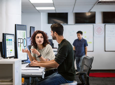 Man and woman at startup company discussing funding at office desk near computer