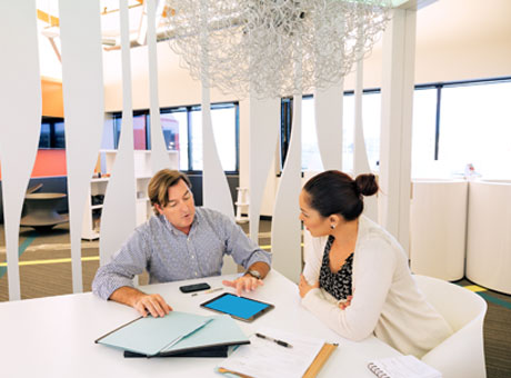 Business professionals at desk in office discussing contra assets
