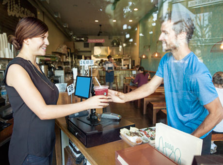 Male and female involved in romatic relationship in restaurant smiling while holding a beverage