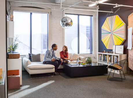 Man and woman small business owners sitting on sofa talking in office lobby with artwork