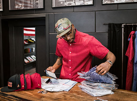 Man organizing vintage clothing for his boutique to help it grow