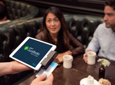 Restaurant waiter swiping business credit card for customers in booth
