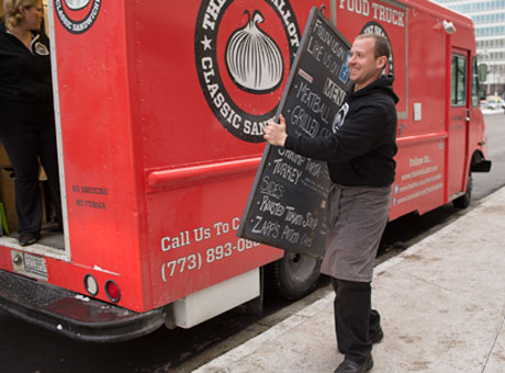 Man working at food truck parked on street carries sign displaying social media marketing information