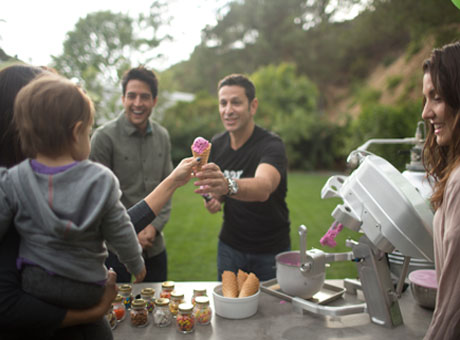 Young entrepreneur at outdoor community event serving ice cream to child and parent