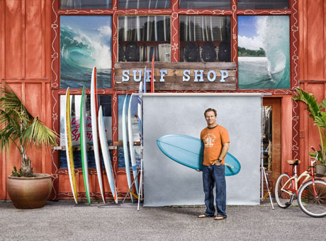Small business owner posing by surf shop holding surf board