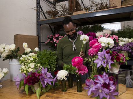 Floral shop employee arranges colorful flowers on table for unique selling point
