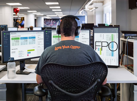 Man with headphones sitting in front of three computer monitors evaluating mind-mapping software