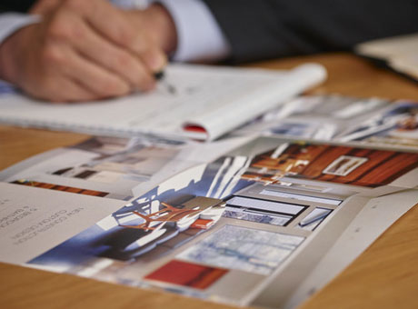 Real estate agent calculating business pay with brochures