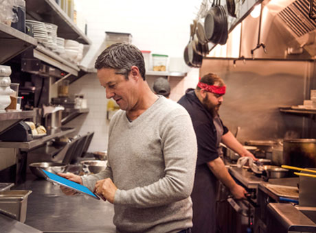 Restaurant owner evaluating business analytics on tablet in kitchen with cook