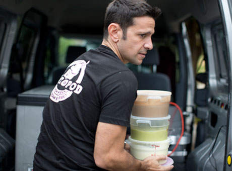 Young man working at an unpaid internship carries tubs of food near a van