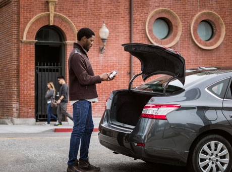 Non-profit employee in front of brick building standing by car viewing smartphone
