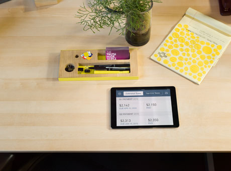 Business invoice on tablet sitting on desk with notepad and flowers