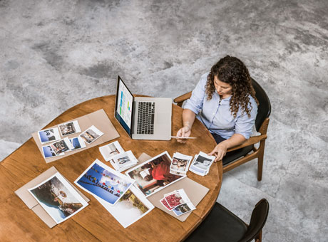 Female payroll employee sitting at table with laptop and photos in view