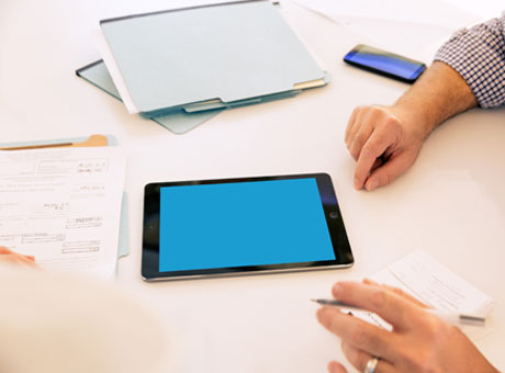 Business professional evaluating multicurrency options on office desk with tablet and paperwork