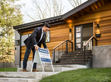 Real estate agent places an open house sign outside a home he is hoping to sell quickly
