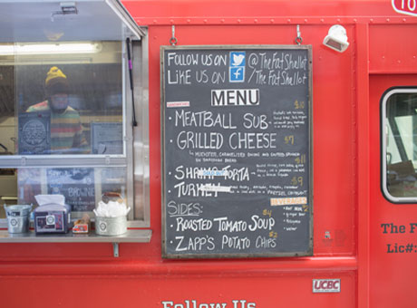 Red food truck displaying menu and campaign on hanging chalkboard