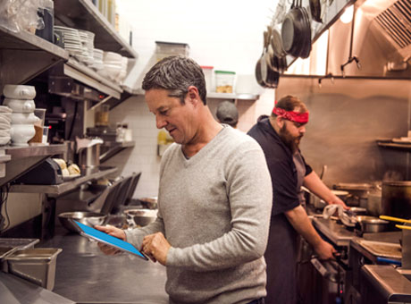 Restaurant salary employee on tablet in kitchen with cook by grill