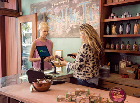 Employee processing payment at retail store for millennial customer by shelves of soap products