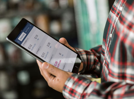 Small business owner creating purchase order on tablet