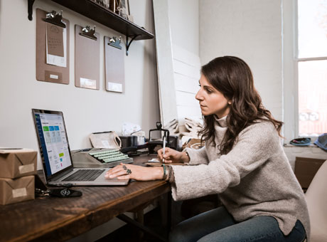 Self-employed woman in office on laptop reviewing tax breaks while sitting at desk
