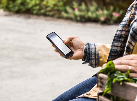 Man on mobile device reviewing payment processing sitting outdoors on farm
