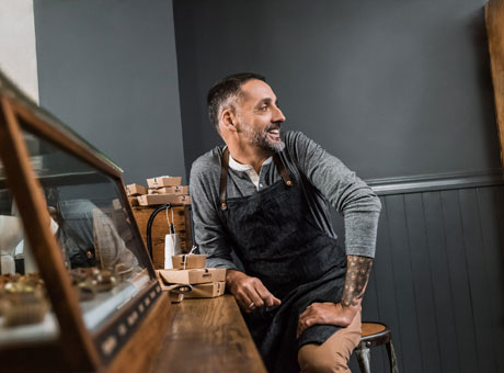Male small business owner sits at wooden workbench near a mirror wearing an apron