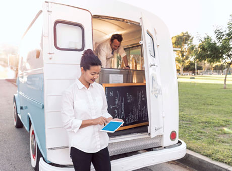 Small business owners on food truck evaluate financials on tablet during economic downtime