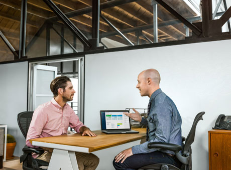 Business professional discussing gross margin with client at office desk near laptop