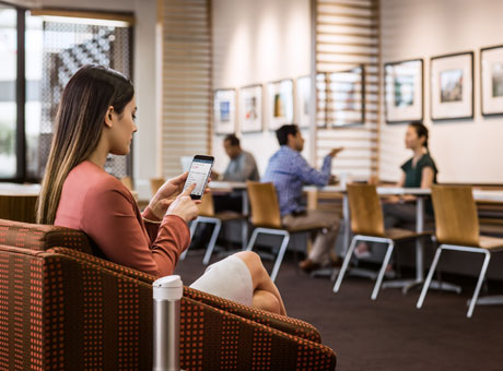 Female in small business lobby viewing business loan information on mobile device