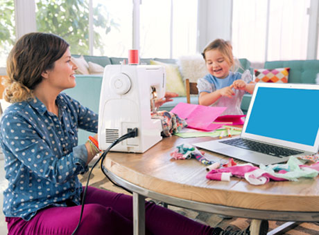 Mom working from home on sewing machine at table with young child