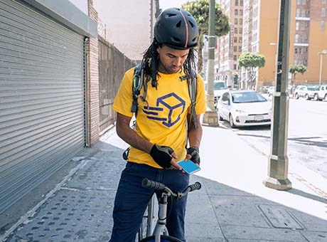 Small business bike delivery rider checks a mobile invoice on his phone