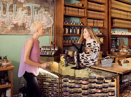 A boutique shop owner completes a sale with a customer