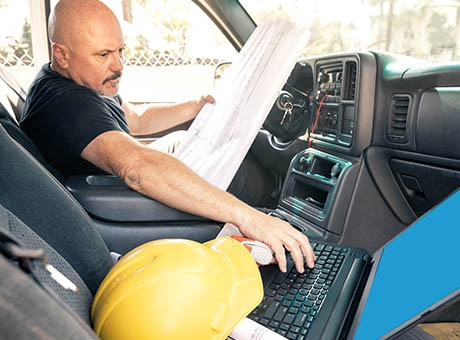 A construction supervisor works in his personal vehicle