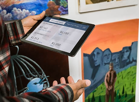 An Etsy seller reviews direct checkout sales on a tablet