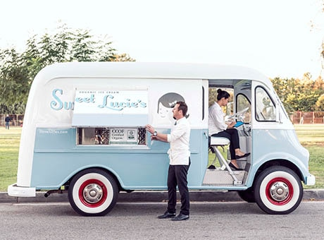 Two employees set a food truck up for a day's business