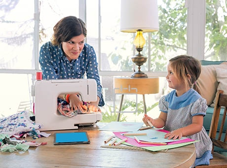 A home business owner sews while her daughter draws at a table