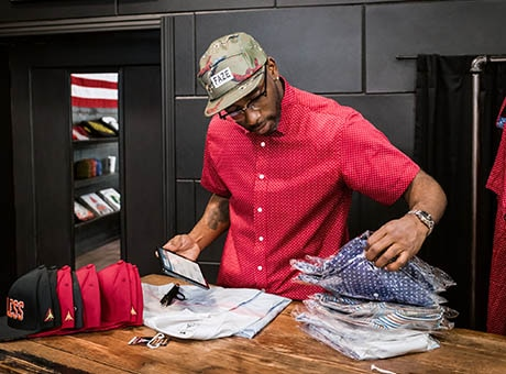 A man prepares a shipment of shirts ordered via e-commerce while holding a tablet
